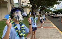 Josh Lee '22 and Kainoa Paul '22 wave to cars waiting in line for the drive-in movie. Photo Courtesy of Punahou School.